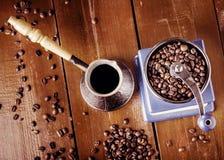 Mechanische koffiemolen, oud koper cezve en koffiebonen Over houten lijst als achtergrond Royalty-vrije Stock Fotografie