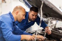 Mechanische mensen die met moersleutel auto herstellen op workshop Royalty-vrije Stock Afbeelding