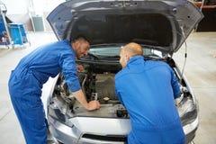 Mechanische mensen die met moersleutel auto herstellen op workshop Royalty-vrije Stock Fotografie