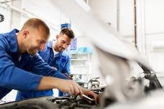 Mechanische mensen die met moersleutel auto herstellen op workshop Royalty-vrije Stock Foto's