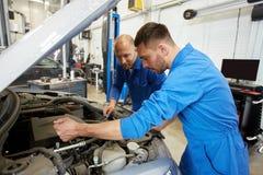 Mechanische mensen die met moersleutel auto herstellen op workshop Stock Foto's