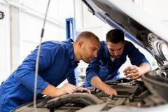 Mechanische mensen die met moersleutel auto herstellen op workshop Stock Foto