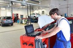 Mechanische reparatiesmotor van een auto met behulp van een dia royalty-vrije stock foto's