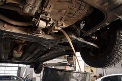 Mechanische veranderende de motorolie van de Profecionalauto in automobiele motor bij het benzinestation van de onderhoudsreparat royalty-vrije stock afbeeldingen