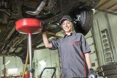 Mechanische vrouw die aan auto in zijn winkel werken stock foto