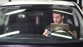 Mechanische zitting in auto die diagnostiek op digitale tablet doen stock footage
