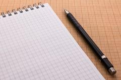 Mechanischer Bleistift und Notizbuch auf Zeichenpapier mit Maßeinteilung stockfoto