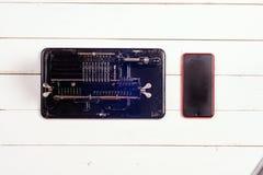 Mechanischer Taschenrechner der Weinlese und modernes Telefon auf einem weißen rustikalen hölzernen Hintergrund Lizenzfreies Stockfoto