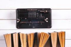 Mechanischer Taschenrechner und Bücher der Weinlese, auf einem weißen rustikalen hölzernen Hintergrund Lizenzfreie Stockfotografie