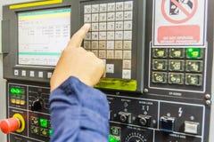 Mechanischer Techniker, der mit Bedienfeld der CNC-Maschinenmitte an der Werkzeugwerkstatt arbeitet Stockbild