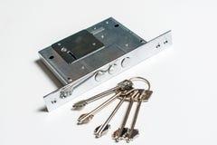 Mechanischer Verschluss mit einem Schlüssel gegen weißen Hintergrund Stockfotografie