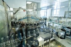 Mechanism of grabbing and turning over of bottles, automatic machine for washing glass bottles. Production and bottling of alcoholic beverages Stock Image