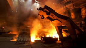 A mechanism with hooks in the hot shop with rising smoke and burning fire at the metallurgical plant. Stock footage. A mechanism with hooks in the hot shop with royalty free stock photography