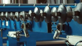 Mechanism of rolling machine. Spinning gears in the machine at the glass factory. color correction. shoot in c-log stock footage