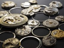 Mechanisms of watches and their parts on a black background. Mechanisms of vintage watches and their parts on a black background stock photo