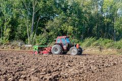 Mechanized crumbling of plowed clay soil. After plowing the field the peasant makes the field ready for sowing. The green colored cultivator and crumbling tool stock image