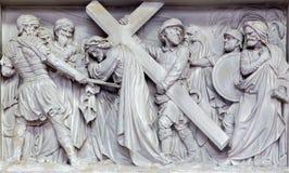 Mechelen - πέτρινη ανακούφιση Simon της βοήθειας Ιησούς Cyrene για να φέρει το σταυρό του στην εκκλησία η κυρία μας πέρα από de D Στοκ Φωτογραφίες