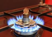 Mechero de gas con la llama azul y las monedas Fotos de archivo libres de regalías