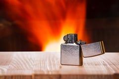 Mechero en la tabla de madera natural delante de un fuego Fotografía de archivo libre de regalías