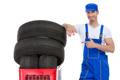 Mecánico alegre que señala en nuevos neumáticos Fotos de archivo