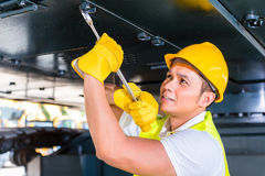Mecânico asiático que repara o veículo da construção Foto de Stock Royalty Free