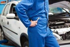 Mecânico com a chave inglesa pelo carro Imagens de Stock Royalty Free
