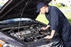 Mecánico de coche que trabaja en servicio de reparación auto. Imagen de archivo