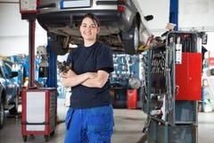Mecánico de sexo femenino joven sonriente en garage Fotos de archivo
