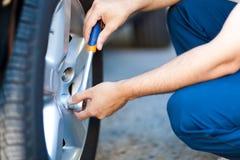 Mecânico em suas pneus ou bordas em mudança da oficina Imagem de Stock