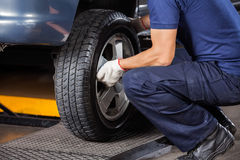 Mecânico Fixing Car Tire na oficina de reparações Imagem de Stock