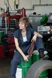 Mecânico fêmea novo feliz que senta-se no cilindro de óleo na oficina de reparações do automóvel Fotografia de Stock