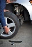 Mecánico que cambia una rueda de un coche moderno Fotos de archivo libres de regalías