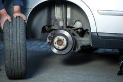 Mecánico que cambia una rueda de un coche moderno Foto de archivo libre de regalías