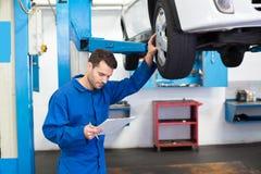 Mecánico que mira los neumáticos de coche Fotos de archivo libres de regalías
