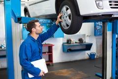 Mecánico que mira los neumáticos de coche Fotografía de archivo