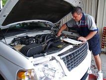 Mecánico que realiza un examen de servicio rutinario Foto de archivo libre de regalías