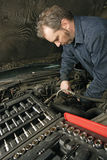 Mecânico que repara um motor Imagens de Stock Royalty Free
