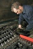 Mecánico que repara un motor Imágenes de archivo libres de regalías