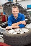 Mecánico que sonríe en la cámara con el neumático Fotos de archivo