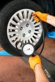 Mecânico que verifica a pressão dos pneus Fotografia de Stock