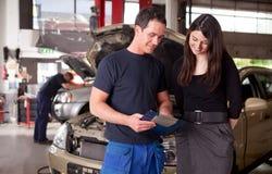 Mecánico y cliente que discuten orden del servicio Imagenes de archivo