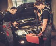 Mecánicos de coche profesionales que examinan la lámpara de la linterna del automóvil en servicio de reparación auto Foto de archivo libre de regalías