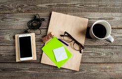 Med anteckningsboken för utrymme för kraft frilansarbete ilar glasögon, blyertspennan, kopp av coffe, biten choklad, telefonen, h arkivbilder