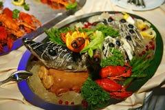 Med Artistically sterleten för den Gefilte fisken som helt bakas, dekoreras en läckerhet från kocken - en maträtt av rådjurskött royaltyfri foto