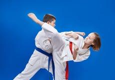 Med det röda och blåa bältet slår barnen karateslag Arkivfoto