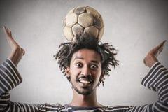 Med en boll på hans huvud arkivfoto