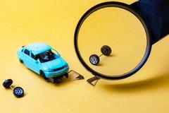 Med en förstoringsglassikt av den brutna bilen på en gul bakgrund royaltyfri fotografi