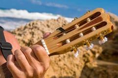 Med en gitarr på ferie vid havet arkivfoton