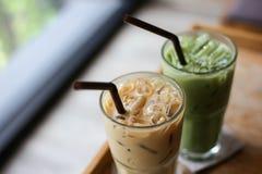 Med is grönt te- och kaffelatte på trätabellen Arkivfoto