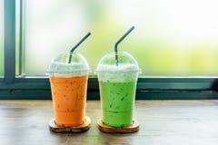 Med is grönt te och thailändskt med is te på den wood tabellen arkivbild